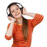 Rozochocona dziewczyna słucha muzyka z hełmofonami obrazy royalty free