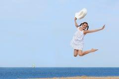 Rozochocona dziewczyna skacze nad wodą przy plażą Zdjęcia Royalty Free
