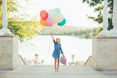 Rozochocona dziewczyna trzyma kolorowych balony i dziecięcą walizkę fotografia stock