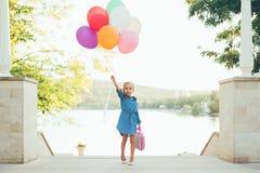 Rozochocona dziewczyna trzyma kolorowych balony i dziecięcą walizkę obrazy royalty free