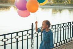 Rozochocona dziewczyna trzyma kolorowych balony i dziecięcego walizki wa Zdjęcia Royalty Free