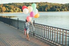Rozochocona dziewczyna trzyma kolorowych balony i dziecięcego walizki wa Zdjęcie Stock