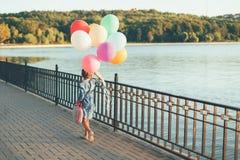 Rozochocona dziewczyna trzyma kolorowych balony i dziecięcego walizki wa Obraz Stock