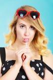 Rozochocona dziewczyna trzyma małego lizaka cukierek w ręce Zdjęcie Stock