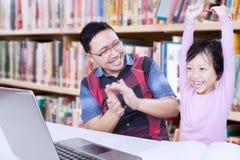 Rozochocona dziewczyna w bibliotece z nauczycielem zdjęcia stock