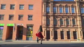 Rozochocona dziewczyna z długie włosy skokami i angażująca w ulicznych tanach po środku kwadrata blisko centrum handlowego zbiory