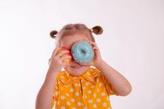 Rozochocona dziewczyna z pączkiem i jabłkiem Obrazy Royalty Free