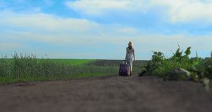 Rozochocona dziewczyna z walizki odprowadzeniem na drodze zdjęcie wideo