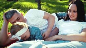 Rozochocona dziewczynka z rodzicami cieszy się pogodnego pogodowego lying on the beach na koc w parku zbiory wideo