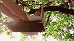 Rozochocona dziewczyny jazda na huśtawce na gałąź dąb w lasowej szczęśliwej dziewczynie jedzie na huśtawce w miasto parku i zbiory wideo