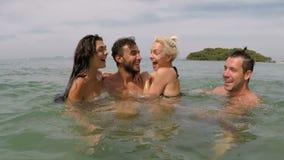 Rozochocona grupa ludzi ma zabawy dopłynięcie w dennej akci kamerze pov młodzi figlarnie przyjaciele na plaży wpólnie zdjęcie wideo