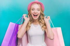 Rozochocona i atrakcyjna dziewczyna trzyma kolorowe torby za ona z powrotem Także jest ubranym różowego kapelusz Odizolowywający  obraz stock