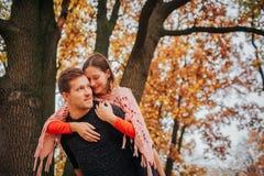 Rozochocona i pozytywna młoda kobieta siedzi na facetów chudy i plecy on Trzyma ona i spojrzenie popierać kogoś Są w jesieni zdjęcie royalty free