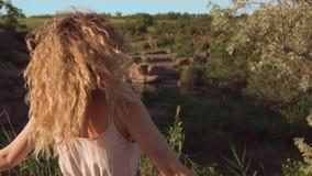 Rozochocona i radosna dziewczyna z blond kędzierzawym włosy wiruje na miejscu, ona kędziory spadają na jej twarzy uśmiech, szczer zdjęcie wideo