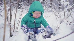 Rozochocona jeden rok chłopiec siedzi w zima lesie i śmia się tworzący z gimbal zbiory