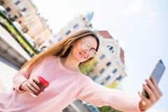 Rozochocona kobieta jest ubranym nowożytnego strój z zadziwiającym uśmiechem robi selfie z kawą na starym rynku podczas gdy space Obrazy Royalty Free