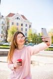 Rozochocona kobieta jest ubranym nowożytnego strój z zadziwiającym uśmiechem robi selfie z kawą na starym rynku podczas gdy space Zdjęcia Stock