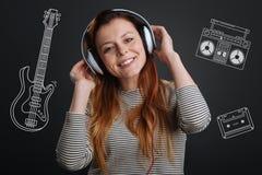 Rozochocona kobieta ono uśmiecha się i słucha muzyka w jej hełmofonach zdjęcie stock
