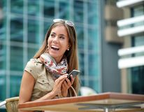 Rozochocona kobieta ono uśmiecha się z telefonem komórkowym Zdjęcie Stock