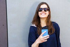 Rozochocona kobieta opowiada fotografię na telefonie w ulicznym przypadkowym o zdjęcia stock