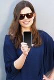 Rozochocona kobieta opowiada fotografię na telefonie w ulicznym przypadkowym o zdjęcie royalty free