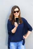 Rozochocona kobieta opowiada fotografię na telefonie w ulicznym przypadkowym o obrazy royalty free