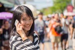 Rozochocona kobieta opowiada na telefonie w ulicie zdjęcia stock