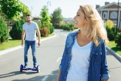 Rozochocona kobieta patrzeje jej męża na hoverboard Zdjęcia Royalty Free
