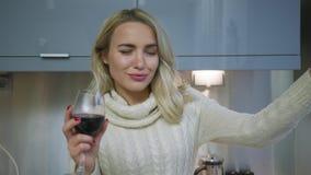 Rozochocona kobieta pije wino w kuchni zbiory