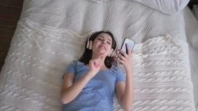 Rozochocona kobieta relaksująca w domu w słuchawki spada na łóżku i słucha piosenki od muzyki telefonu komórkowego i zachw zbiory wideo