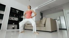 Rozochocona kobieta robi pękatemu ćwiczeniu i patrzeje na mądrze zegarku w domu zbiory wideo