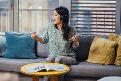 Rozochocona kobieta słucha muzyka z wielkimi hełmofonami i śpiewem Cieszący się słuchać w domu muzyka w czasie wolnym Relaksować  obraz royalty free