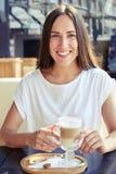Rozochocona kobieta trzyma filiżankę cappuccino Fotografia Stock
