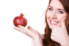 Rozochocona kobieta trzyma granatowiec owoc, odizolowywa? obraz stock