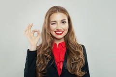 Rozochocona kobieta uśmiecha się ok znaka i pokazuje obraz stock