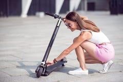 Rozochocona kobieta używa kopnięcie hulajnoga fotografia stock