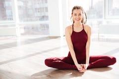 Rozochocona kobieta uśmiecha się joga w studiu i robi Obraz Royalty Free