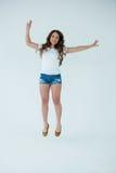 Rozochocona kobieta w białej koszulki i gorących spodń skakać zdjęcia royalty free