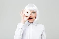 Rozochocona kobieta w blondynki peruce zakrywał jej oko z pączkiem Zdjęcia Royalty Free