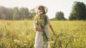 Rozochocona kobieta w słomianym kapeluszu z kwiatami w łące zdjęcie wideo