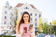 Rozochocona kobieta w ulicznej pije ranek kawie i używa jej smartphone kobieta sms - ów Obraz Stock