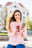 Rozochocona kobieta w ulicznej pije ranek kawie i używa jej smartphone kobieta sms - ów Fotografia Stock