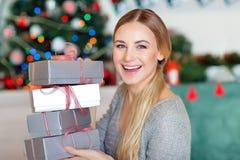 Rozochocona kobieta z Bożenarodzeniowymi prezentami zdjęcie royalty free