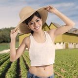Rozochocona kobieta z kapeluszem przy ziemią uprawną Zdjęcia Stock