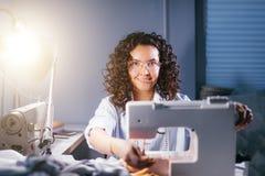 Rozochocona krawcowa nastraja szwalną maszynę dla pracy przy zaświecającym studiiem zdjęcia stock