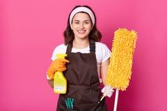 Rozochocona młoda gospodyni domowa jest ubranym białą t koszula, brązu fartuch z zielonymi clothespins, pomarańczowe gumowe rękaw obraz royalty free
