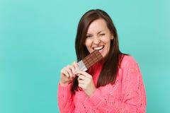 Rozochocona młoda kobieta w trykotowym różowym puloweru mieniu w ręce, gryźć czekoladowego baru, mrugać odizolowywam na błękitnym obrazy royalty free
