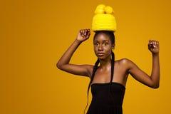 Rozochocona młoda afrykańska kobieta z żółtym makeup na ona oczy Kobieta model przeciw żółtemu tłu z żółtymi cytrynami obraz stock
