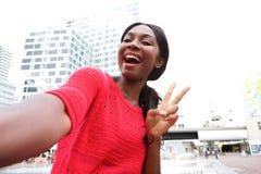 Rozochocona młoda amerykanin afrykańskiego pochodzenia kobieta bierze selfie w mieście obrazy royalty free
