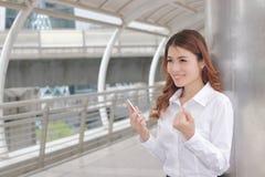 Rozochocona młoda Azjatycka biznesowa kobieta z mobilnymi mądrze telefonu dźwigania rękami przy outside biurem Fotografia Royalty Free